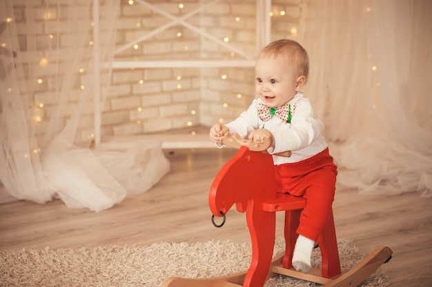 Porträt eines reizenden kleinen jungen, der einen schaukelhirsch reitet