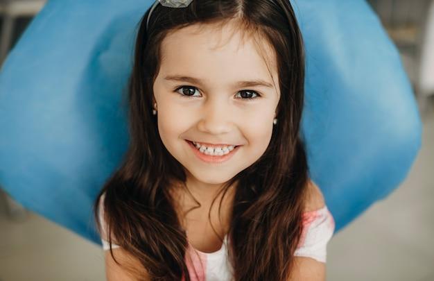 Porträt eines reizenden kleinen mädchens, das in einer pädiatrischen stomatologie sitzt und kamera betrachtet, die vor zahnoperation lacht.