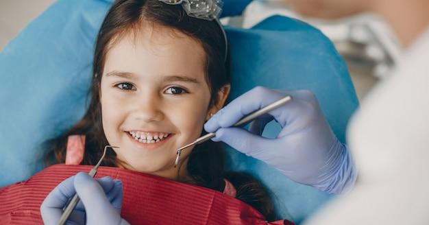 Porträt eines reizenden kleinen mädchens, das kamera lächelnd beim sitzen in einer pädiatrischen stomatologie nach zahnuntersuchung betrachtet.