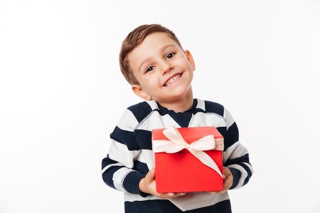 Porträt eines reizenden niedlichen kleinen kindes, das geschenkbox hält