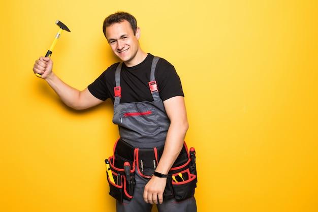 Porträt eines reparaturmanns, der einen hummer erhebt und anfängt, isoliert auf gelbem hintergrund zu arbeiten
