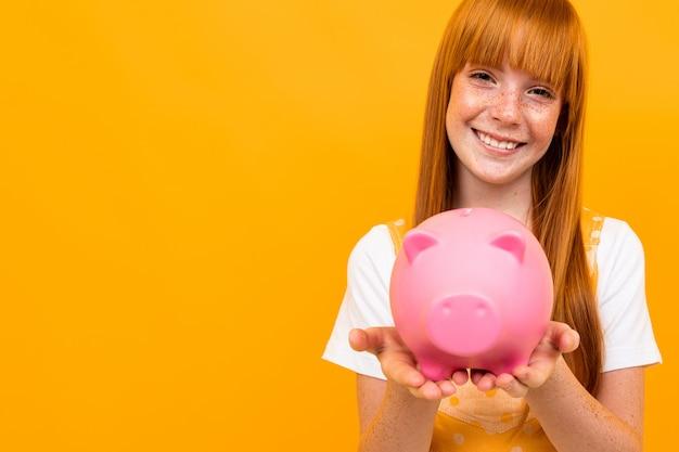 Porträt eines rothaarigen mädchens, das ein sparschwein in den händen auf einem gelb hält