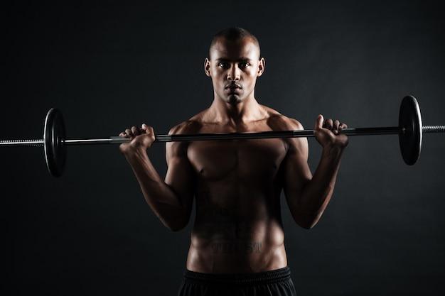 Porträt eines safroamerikanischen sportmannes, der übungen mit langhantel macht