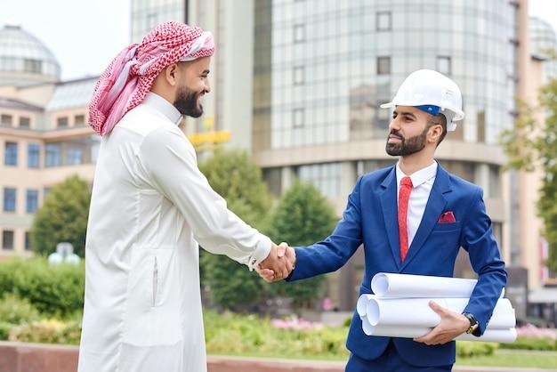 Porträt eines saudischen geschäftsmannes, der einem architekten im freien auf der sich entwickelnden stadt die hand schüttelt