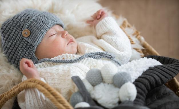 Porträt eines schlafenden babys in einer warmen strickmütze mit einem gestrickten spielzeug in der griffnahaufnahme.