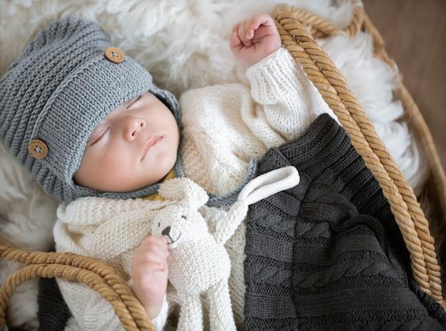 Porträt eines schlafenden babys in einer weidenwiege in einer warmen strickmütze unter einer warmen decke mit einem spielzeug im griff.