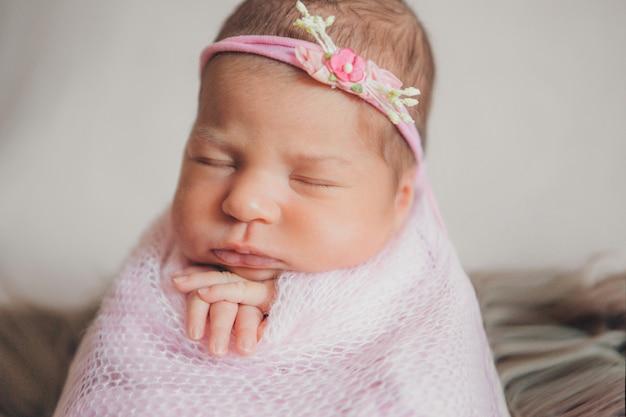 Porträt eines schlafenden neugeborenen in einem stirnband mit blume. gesundheitskonzept: ivf, babyzubehör