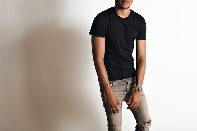 Porträt eines schlichten schwarzen baumwoll-kurzarm-t-shirts auf einem athletischen schwarzen oder lateinamerikanischen mann mit weißen wänden