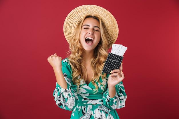 Porträt eines schockierten aufgeregten jungen blonden mädchentouristen in hellblauem kleid, das isoliert über roter wand posiert und reisepass mit tickets hält, macht siegergeste