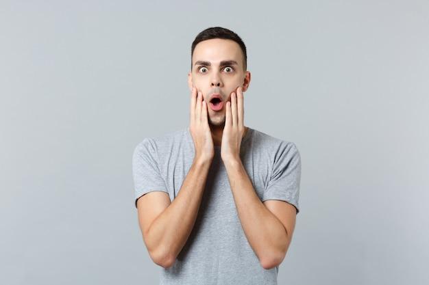 Porträt eines schockierten aufgeregten jungen mannes in freizeitkleidung, der den mund offen hält und die hände auf das gesicht legt