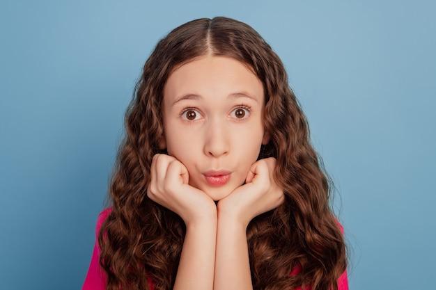 Porträt eines schockierten aufgeregten kleinen mädchens mit offenen armen und offenem mund auf blauem hintergrund