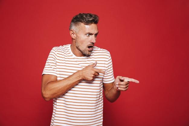 Porträt eines schockierten erwachsenen mannes der 30er jahre, der mit dem finger auf das exemplar isoliert auf rot zeigt