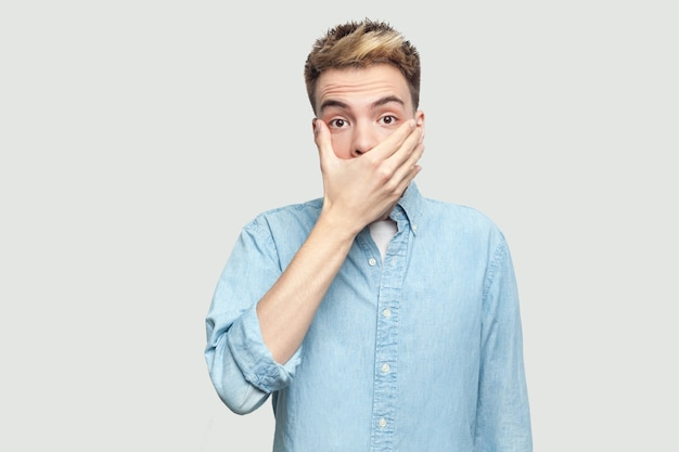 Porträt eines schockierten, gutaussehenden jungen mannes in hellblauem hemd, der mit verängstigtem gesicht steht, seinen mund bedeckt und die kamera mit großen augen betrachtet. innenstudio auf grauem hintergrundkopierraum gedreht.