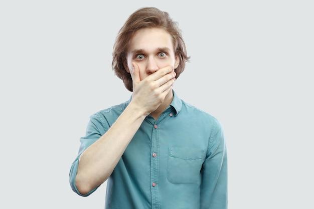 Porträt eines schockierten, gutaussehenden, langhaarigen, blonden jungen mannes in blauem freizeithemd, der seinen mund bedeckt und mit großen augen in die kamera schaut. indoor-studioaufnahme, isoliert auf hellgrauem hintergrund.