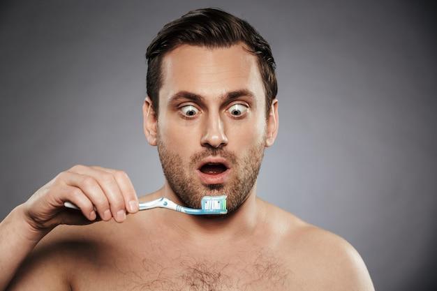 Porträt eines schockierten hemdlosen mannes, der zahnbürste hält