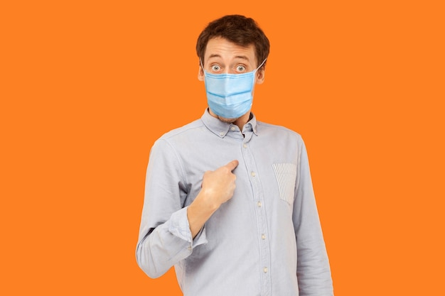 Porträt eines schockierten jungen arbeitermannes mit chirurgischer medizinischer maske, der auf sich selbst zeigt, fragt und mit erstauntem gesicht in die kamera schaut. indoor-studioaufnahme auf orangem hintergrund isoliert.