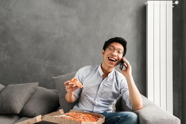 Porträt eines schockierten jungen asiatischen mannes, der pizza isst