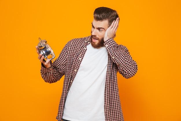 Porträt eines schockierten jungen mannes, der freizeitkleidung hält wecker hält