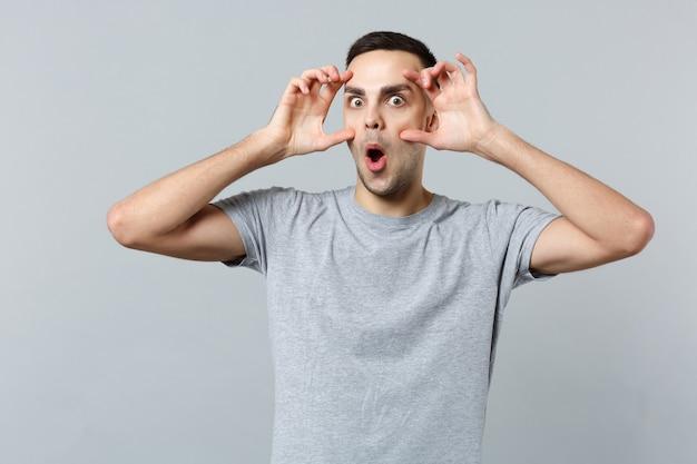 Porträt eines schockierten jungen mannes in freizeitkleidung, der den mund weit offen hält und die augenlider ausdehnt