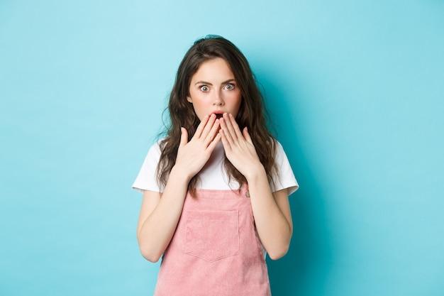 Porträt eines schockierten klatschmädchens, das nach luft schnappt, den geöffneten mund mit den händen bedeckt und erschrocken in die kamera starrt, ein gerücht hört, ungläubig schaut und vor blauem hintergrund steht.