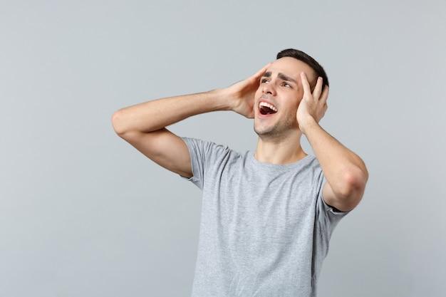 Porträt eines schockierten, schreienden jungen mannes in freizeitkleidung, der beiseite schaut und die hände auf den kopf legt