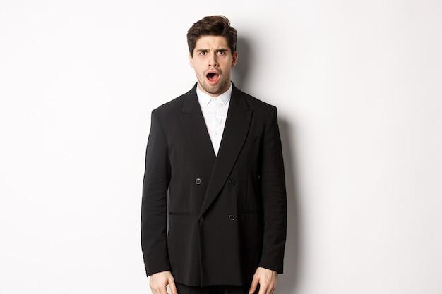 Porträt eines schockierten und erschrockenen gutaussehenden mannes in anzug, kiefer und blick in ehrfurcht in die kamera, stehend auf weißem hintergrund.