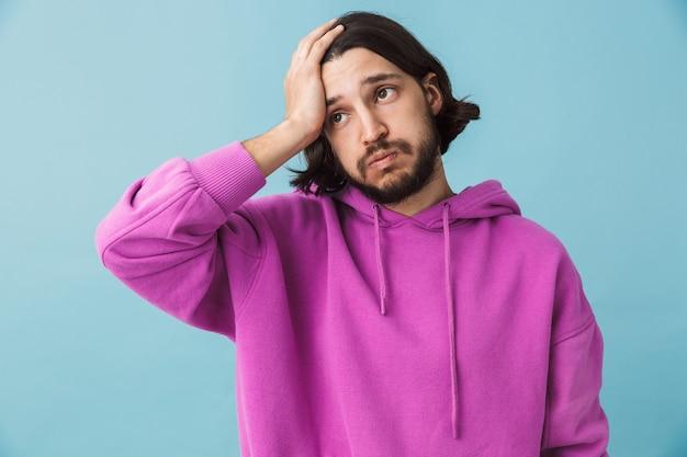 Porträt eines schockierten verwirrten jungen bärtigen brünetten mannes mit hoodie, der isoliert über blauer wand steht