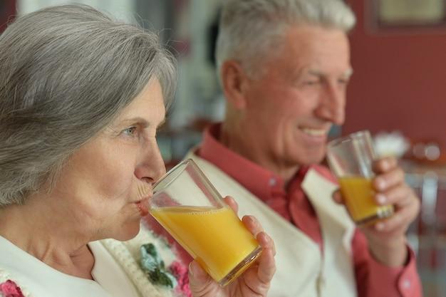 Porträt eines schönen älteren paares, das saft trinkt