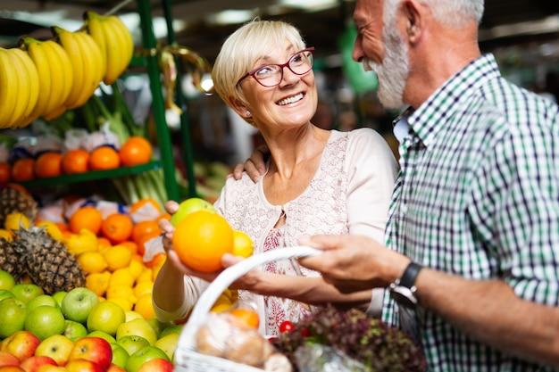 Porträt eines schönen älteren paares im markt, der lebensmittel kauft?