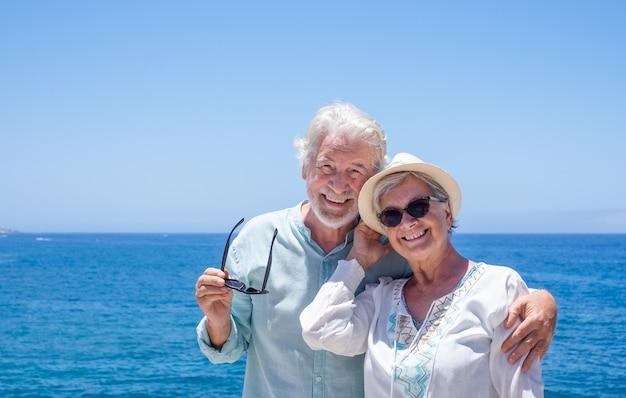 Porträt eines schönen älteren paares umarmte sich vor dem meer, das kamera betrachtet. glückliche rentner, die am strand stehen und die sommerferien genießen