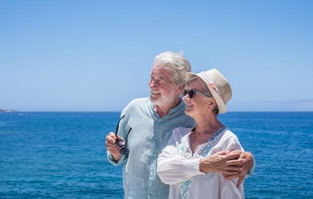 Porträt eines schönen älteren paares umarmte sich vor dem meer und schaute weg. glückliche rentner, die am strand stehen und die sommerferien genießen
