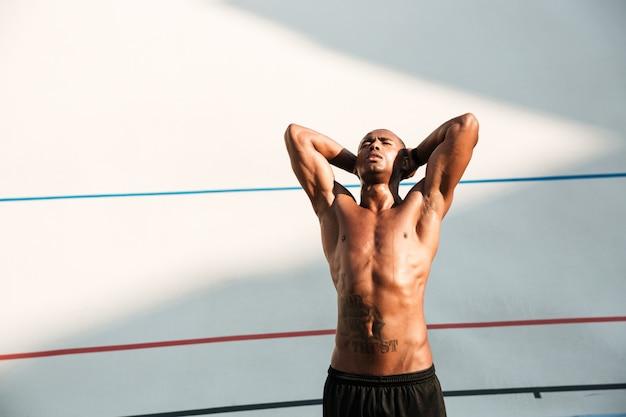 Porträt eines schönen afrikanischen läufers, der nach lauf auf stadion ruht