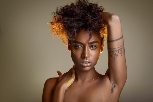 Porträt eines schönen afrikanischen modells mit unrasierter achselhöhle. natürliche schönheit. körper positiv