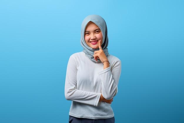 Porträt eines schönen asiatischen frauenlächelns mit verschränktem arm und erhobener hand am kinn