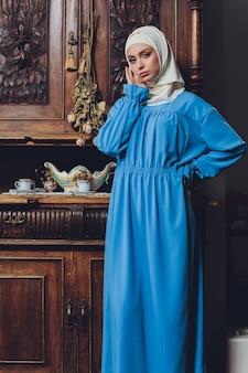 Porträt eines schönen asiatischen muslimischen frauenmodells, das weiße bluse und blauen hijab trägt, der auf weißem vorhang als hintergrund in nahaufnahmeansicht aufwirft