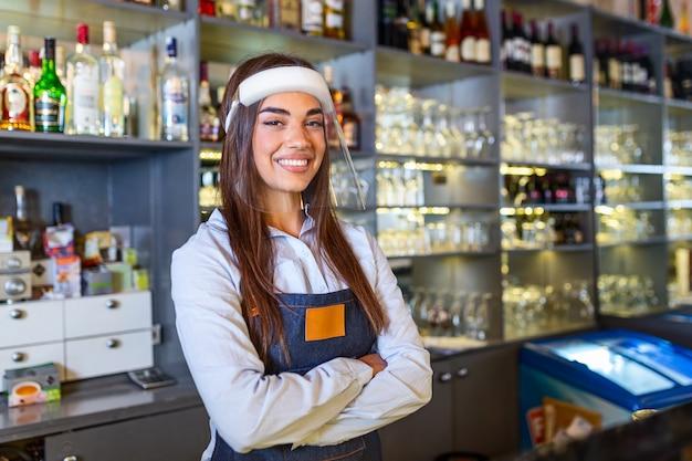 Porträt eines schönen barkeepers, der lächelnd an der theke steht und in die kamera schaut, während er gesichtsschutz wegen covid-19 trägt, regale voller flaschen mit alkohol auf dem hintergrund