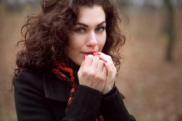 Porträt eines schönen blauäugigen mädchens, das gefrorene hände wärmt