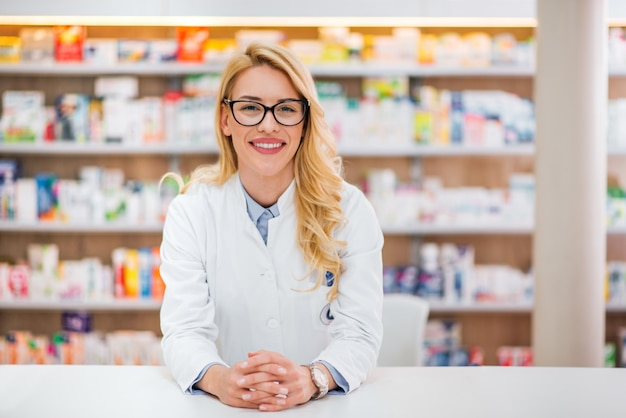 Porträt eines schönen blonden apothekers, der auf zähler am pharmazeutischen speicher sich lehnt.