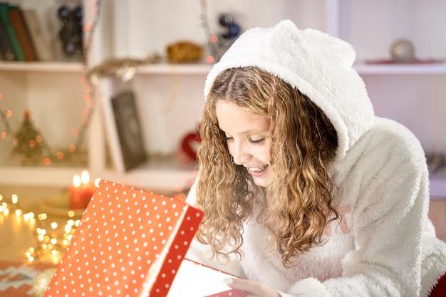 Porträt eines schönen blonden jungen mädchens glücklich mit geschenkbox