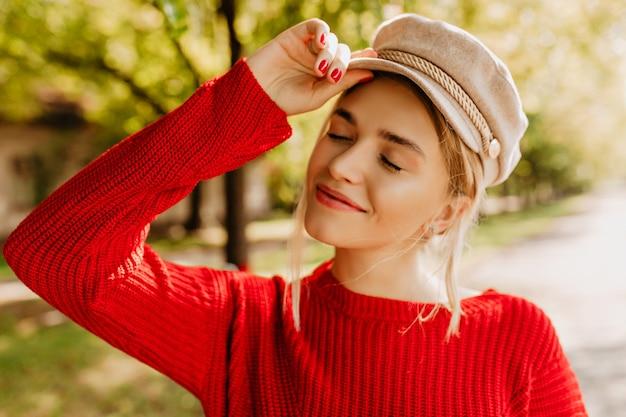 Porträt eines schönen blonden mädchens im schönen roten pullover und im hellen hut, der im herbstpark aufwirft.