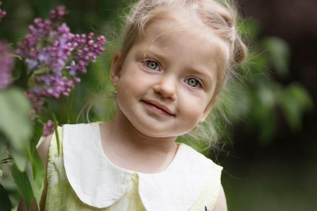 Porträt eines schönen blonden mädchens mit verschwommenem flieder auf dem hintergrund