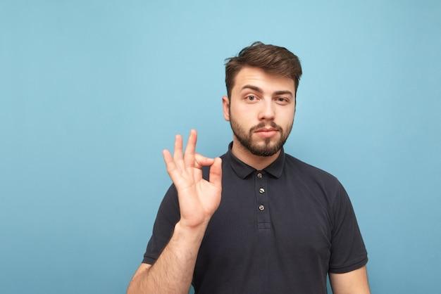 Porträt eines schönen brünetten mannes, der ein dunkles hemd mit einem bart trägt, der auf blau steht und eine geste des ok mit seiner hand zeigt