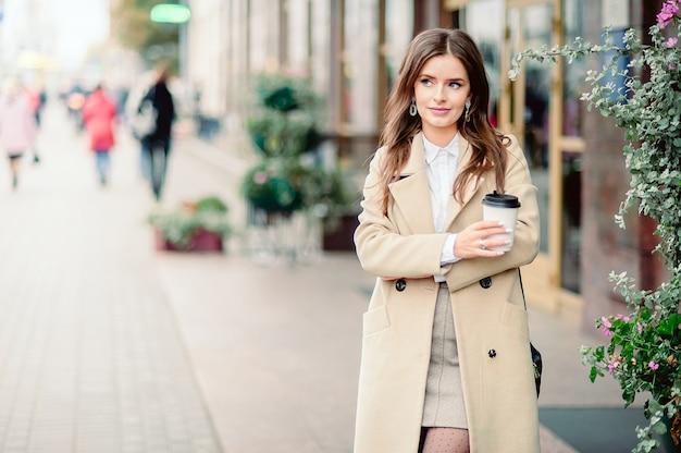 Porträt eines schönen brunettemädchens, das entlang die straße geht. einweggeschirr zum mitnehmen in einer hand halten. lächelt. städtische szene der stadt. warmes sonniges herbstwetter. auf der strasse