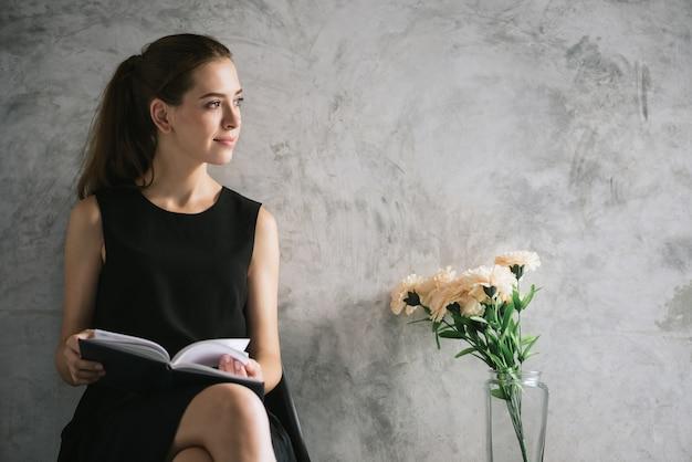 Porträt eines schönen buches der jungen frau lese, das im wohnzimmer sich entspannt. vintage effekt stil bilder.