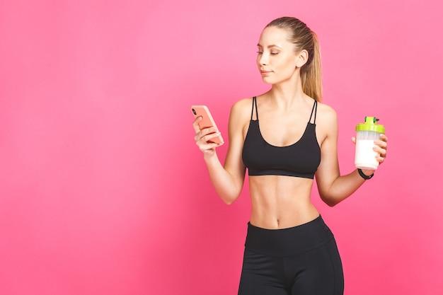 Porträt eines schönen fitness-mädchens mit einem fitness-shaker unter verwendung des telefons