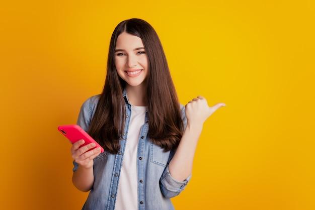 Porträt eines schönen fröhlichen mädchens, das in den händen hält, telefonieren direkt mit der daumenseite leerer raum