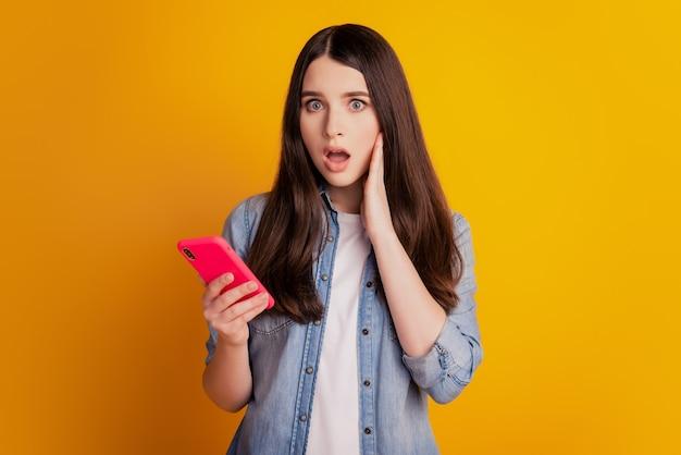 Porträt eines schönen fröhlichen mädchens, das in den händen hält, telefonieren verrückter reaktions-look-bildschirm