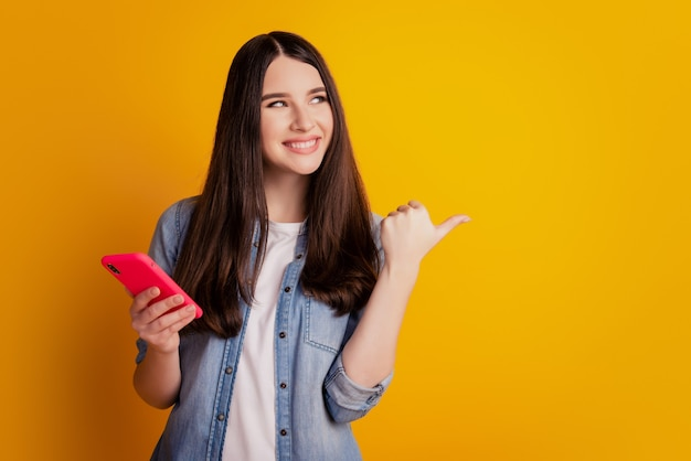 Porträt eines schönen fröhlichen mädchens, das in den händen hält, zeigt eine handy-look-seite an, die auf einen leeren raum hinweist