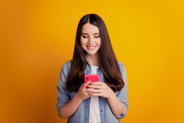 Porträt eines schönen fröhlichen mädchens, das in den händen smartphone-look-bildschirm hält, der ein zahniges lächeln plaudert