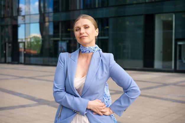 Porträt eines schönen geschäfts einer erfolgreichen frau in einer blauen jacke auf dem hintergrund eines bürogebäudes